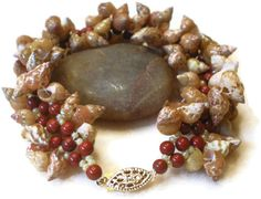 """Got Shells? Hand woven red jasper and glass beads with outside edges loaded with small cone shells. Clasp is gold filled """"safety hook"""" style. Length is 7 3/4 inches long.This is not just for summer. The colors will look great in the fall with the earth tones of the red jasper and the gold clasp."""