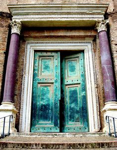 Ancient turquoise doors between purple columns in Rome, Italy