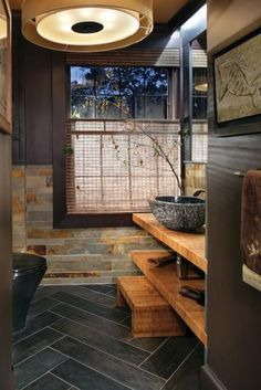 Natural materials make a strong design statement in this powder room.  Slate walls, a herringbone wood-grain porcelain tile floor, a black granite vessel sink, two thick bamboo cantilevered counter surfaces, and cherry cabinets. Beautiful.