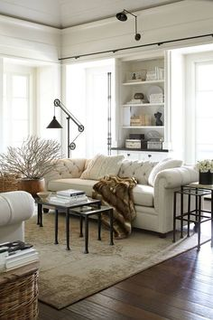Beautiful neutral living room with tufted couch, nesting tables, and industrial lamp.