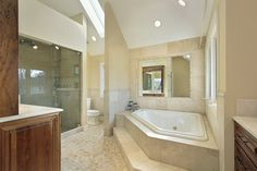 Bathroom with vaulted ceiling, extensive marble, wood work, sunken tub and separate glass shower