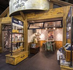 The YETI Coolers booth at Outdoor Retailer show featured several fun conference rooms. This one, enclosed by a glass garage door, had a custom-made surfboard table! Other features of the exhibit include repurposed barn wood structural elements and displays, a double-decker conference space, and vintage truck trailer.