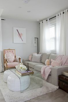 pale pink chair with gold details, light grey sofa with cushions and pink blanket, clear glass table and two white bean floor cushions, fluffy cream rug, window with white curtains