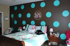 Bold turquoise polka dots on dark wall, with initials in center and peace sign quilt.  Fun!