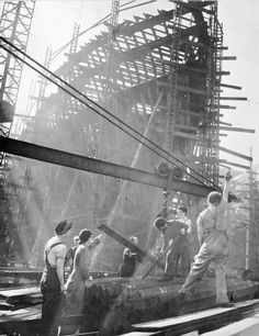 Women shipbuilders giving the signal for the lifting of steel girders at a shipyard in Britain.