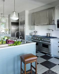 Stunning kitchen features white upper cabinets and blue lower cabinets paired with white quartzite ...