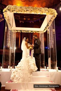 Plexiglass chuppah/ceremony structure covered with white blooms. Photo by Shira Weisberger.