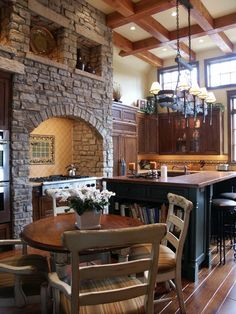Towering stone hearth with niches to repeat the clerestory windows in this Lodge Style kitchen