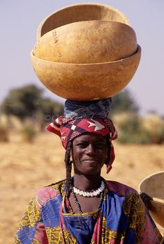 Delaquara, Niger. Fulani Woman Balancing Empty Calabashes on Head, wearing Necklace of Cowrie Shells.