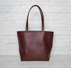 Very Very Soft, Supple,Lightweight Beautiful Dark Maroon cow leather Tote bag. This Beautiful Leather Tote Bag is Roomy enough for all your daily essentials and would work great all year round.  The leather handles are strong enough to carry your laptop, Books and fit comfortably over your shoulder. The bag is fully lined with thick Gray canvas with 5 interior pockets.