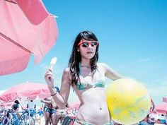 Young women in shades and a bikini poses with an ice lolly and a beach ball.