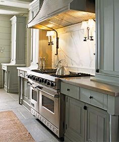 """BENJAMIN MOORE GREAT BARRINGTON GREEN: """"Especially in a small kitchen, people don't think of dark colors as an option, but that's exactly where you need the drama. This is a lovely gray-green, not too dark and very soft, kind of like moss. Very elegant with white cabinets."""" -Mick de Giulio   - HouseBeautiful.com"""