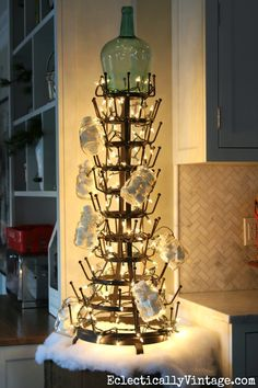What a fun idea for a kitchen Christmas tree! String some lights around a huge bottle drying rack! eclecticallyvintage.com