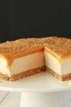 Vegan Cheesecake on a white cake stand with one slice removed from it.