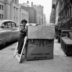 Like an kid he is curious what's in the box.  Street Photography 1 | Vivian Maier Photographer