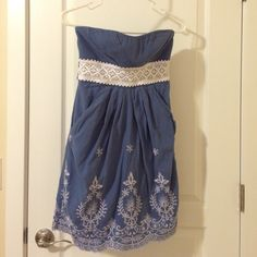 Beautiful blue embroidered dress! Country blue with white embroidery and trim. Strapless with ties in back. Front pockets. Dresses