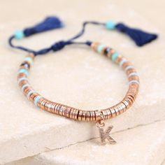 This on-trend rose gold ladies' bracelet from the exclusive Lisa Angel Delicate range, with initial personalisation, is perfect for summer style.<em>Personalisation: choose between rose gold plated heart, star or initial shaped charms and the initial of your choice.</em><ul> <li>A beautiful bohemian inspired tassel bracelet with rose gold plated discs and turquoise coloured beads strung along a navy cord.</li> <li>With square sliding adjuster knot.</li> <li>From the Lisa Angel Jewellery…