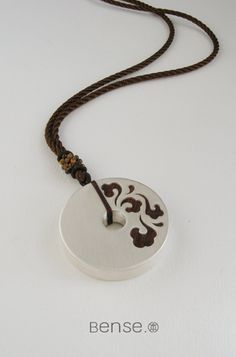 Silver pendant with embedded wood pattern.