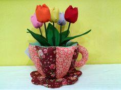xícara em tecido 100% algodão com enchimento de fibra siliconada. acompanha arranjo de tulipas em um potinho de plástico com argila e coberto com musgo. Pode-se retirar o arranjo. Consultar estampas disponíveis antes de efetuar o pagamento.