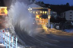 Waves crash over the promenade at hightide in Saundersfoot, in west Wales in the early morning of January 3. (Reuters/Rebecca Naden)