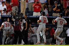 Pete Kozma and Matt Carpenter of the St. Louis Cardinals run into the dugout as fans throw debris onto the field after an infield fly was called in the eighth inning against a ball hit by Andrelton Simmons of the Atlanta Braves during the National League Wild Card playoff game at Turner Field on October 5, 2012 in Atlanta, Georgia.