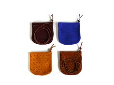 """The convertible pouch is punched to create a perforated peg board like pattern on the face. It has a brass zipper, leather zipper pull, and detachable strap. Dimensions: 7H"""" x 7W"""".  Strap length is fully adjustable.The Dot Pouch is available in ultramarine blue suede, mustard, rust, and burgundy.  Much like denim, dyed suede may rub off on lighter colors if conditions permit. Protect suede with a suede leather spray.**All products are made to order.  Please allow 5..."""