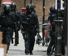Armed police carry equipment outside a building near Tottenham Court Road in central London. (AP)