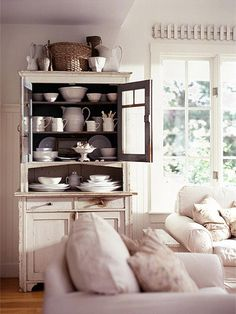Cottage Cabinet Displays - In this sunroom, a favorite china cabinet wears its original paint--white outside and sage green within. It's a soothing backdrop for a collection of white ironstone. Gathering collections in a spare palette creates harmony. Cottage Style Living Room, Coastal Living Rooms, Formal Living Rooms, Living Room Decor, Coastal Cottage, Cozy Cottage, Coastal Decor, Living Spaces, Dining Room