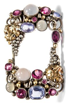 Dorrie Nossiter - An Arts and Crafts silver, gold and gem-set brooch, English, circa 1935. Set with Ceylong sapphires, moonstones and rhodolites, mounted in silver and yellow gold. 3.2 x 5.4cm. #Nossiter #ArtsAndCrafts #brooch