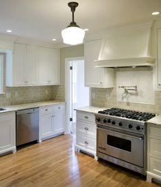 Green tile, white cabinets, wood floor.