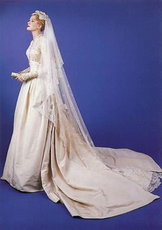 """Grace Kelly's Wedding Dress - """"The wedding dress consisted of a rounded collar, full skirt of ivory peau de soie, and a fitted bodice made from Brussels lace embroidered with seed pearls. The lace was over a century old and had flower designs in it. 25 yards of silk taffeta and 100 yards of silk net were used in the construction of the dress. Under her wedding gown, Grace's petticoats had tiny blue satin bows."""""""