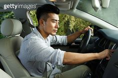 Young man driving and using GPS system in car