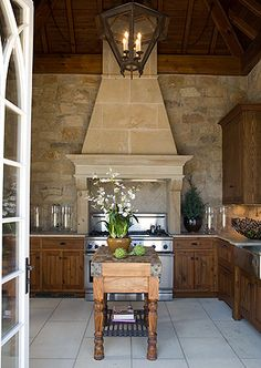 Gorgeous Kitchen with rich wood cabinetry, Island & Ceiling & beautiful Stone above stove & on the walls - by   Anne Decker Architects