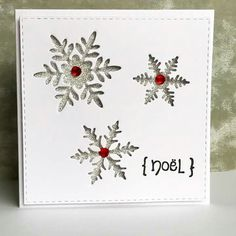 handmade Christmas card ... negative space die cut snowflakes back with silver glitter paper ... spots of red from centered gems ... luv the clean and simple layout ...