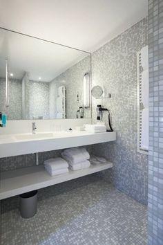 Szara mozaika w hotelowej łazience sprawia, ze jest ona elegancka, ale nie monotonna. W takim wnętrzu należy ograniczyć liczbę dodatków, ponieważ mozaika sama w sobie jest dominująca.
