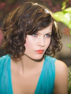 Well executed curly graduated bob. Also on trend - good use of coral lipstick.