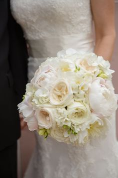 White and blush bouquet featuring peonies, hydrangea, garden roses, and freesia. Photo courtesy of Meg Baisden Photography.