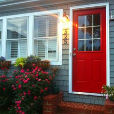 Red door, gray shingle siding and pretty flower boxes = beautiful bungalow