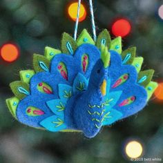 peacock-ornament-pattern by Betz White Today's the third pattern reveal of the 2018 Holiday Stitch-along Ornament Club! Introducing the Peacock Ornament! Felt Christmas Decorations, Felt Christmas Ornaments, Christmas Crafts, Peacock Christmas, Homemade Christmas, Christmas Christmas, Tree Decorations, Peacock Ornaments, Ornaments Design