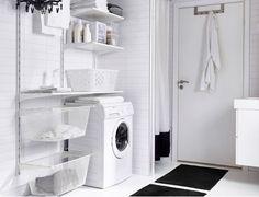 Un lavadero con estantes de pared blancos, cajas de diferentes tamaños y un tendedero