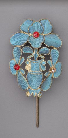 Hair ornament  China, Qing dynasty (1644 - 1911), Late 19th century - early 20th century, Kingfisher feather, gilt metal, glass and stone, 13 x 3.8 x 0.6 cm, Washington, Freer / Sackler