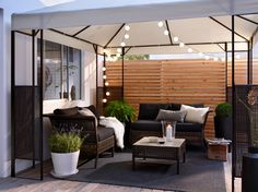 A patio with two sofas and a table in black-brown plastic rattan with black seat/back cushions. All gathered under a gazebo with outdoor lighting chains.