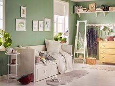 Habitación pequeña con un diván blanco combinado con una cómoda de pino macizo tintado en amarillo y un espejo de pie blanco.
