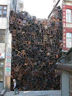 """Instalação de Doris Salcedo (Bogotá, 1958) para a Bienal de Istambul, em 2003. 1600 cadeiras de madeira empilhadas num espaço vazio entre dois edifícios. """"Lixo""""."""