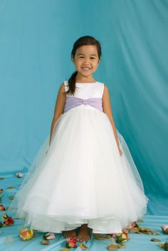 Eden 12283 Flower Girl Dress Matte Satin and Tulle ball gown featuring a sleeveless bodice and modified taffeta bow at the waistline The full gathered floor length skirt is accented around the waistline by scattered sequins A small train finishes the look Available in all tulle colors in combination w/any satin or taffeta colors #timelesstreasure