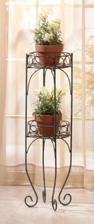 Lacy scrolls in a verdigris-style finish comprise this two-shelf plant stand. A graceful addition for indoors or out; shelves securely hold two of your favorite plants!
