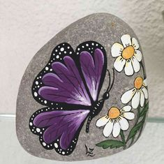 Butterfly on a rock valentine paint rock - Crafts Rock Ideas - Do you need rock painting ideas for spreading rocks around your neighborhood or the Kindness Rocks Project?Purple Butterfly with Daisies Flowers painted rock art. Rock Painting Patterns, Rock Painting Ideas Easy, Rock Painting Designs, Paint Designs, Butterfly Painting Easy, Painting Flowers, Painted Rock Animals, Painted Rocks Craft, Hand Painted Rocks