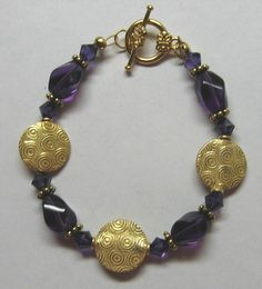 This pretty gold coin bracelet is enhanced by synthetic (man made) amethyst and purple swarovski bicones. It is finished with a lovely gold plated floral toggle clasp. Coin Bracelet, Bracelets, Gold Coins, Swarovski Crystals, Cuffs, Amethyst, Gemstones, Jewellery, Purple