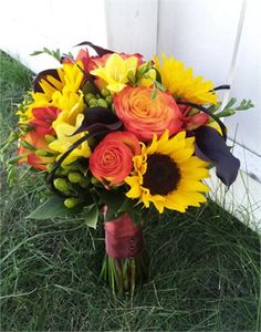 Bright collection of Fall colored flowers accented with wisps of feathers.