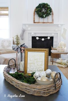 Filling a basket with bowls of ornaments on your coffee table is a great way to inexpensively decorate for the holidays. Add a framed printable and a lantern creates a nice seasonal display using affordable accessories from HomeGoods. Sponsored Pin.